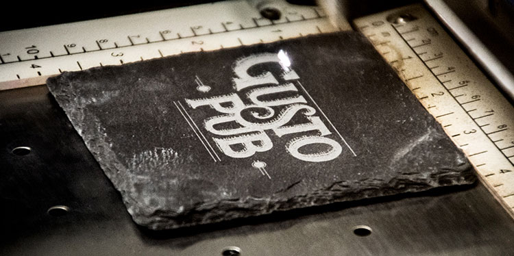 Slate coasters being engraved with a logo