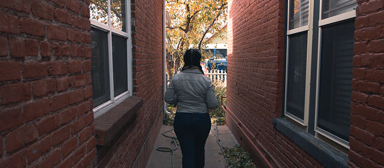 Woman walking down alleyway on bright fall day.