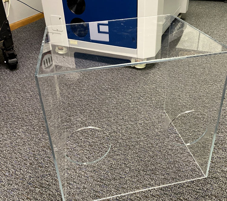 Laser cut acrylic aerosol box sitting on the floor