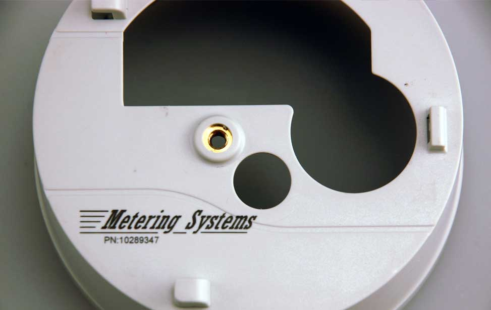 White plastic part marked with a laser, turning the engraved area black.