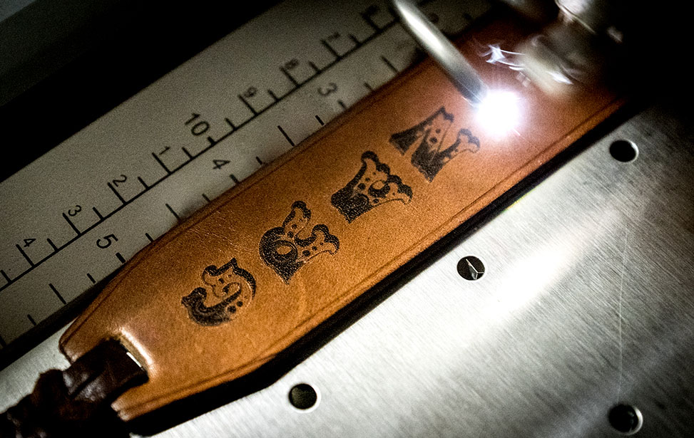 A leather bookmark being laser engraved