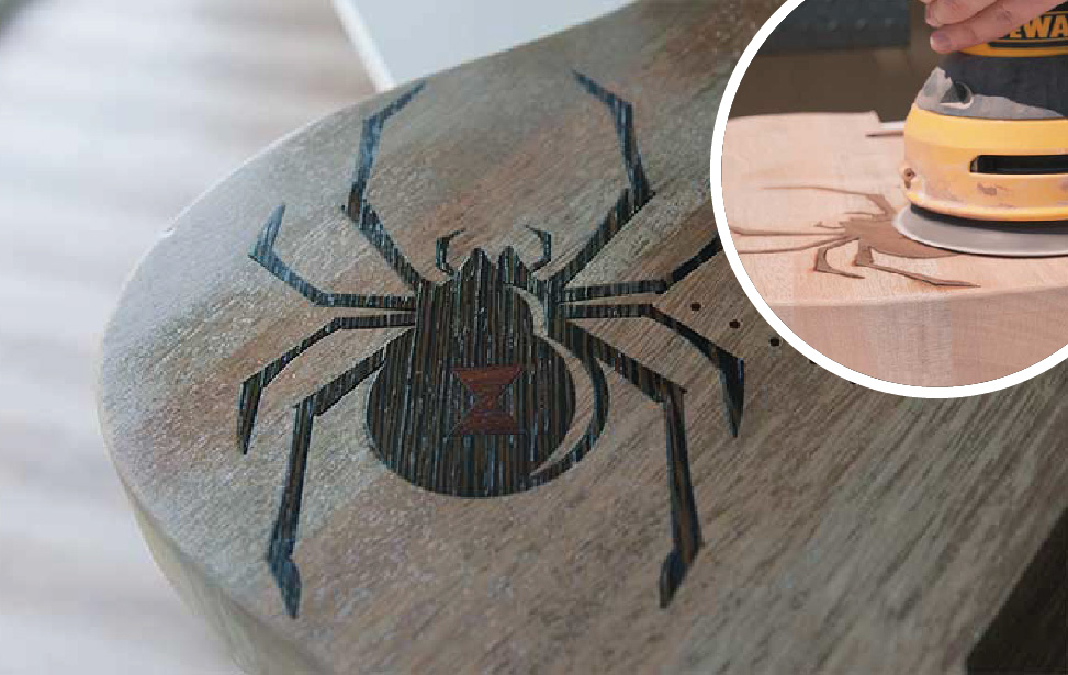 Spider graphic inlaid into a wooden guitar body.