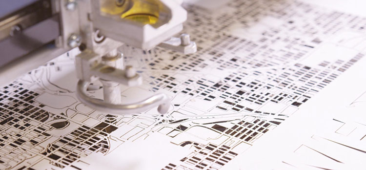 Laser cutting a paper city map.