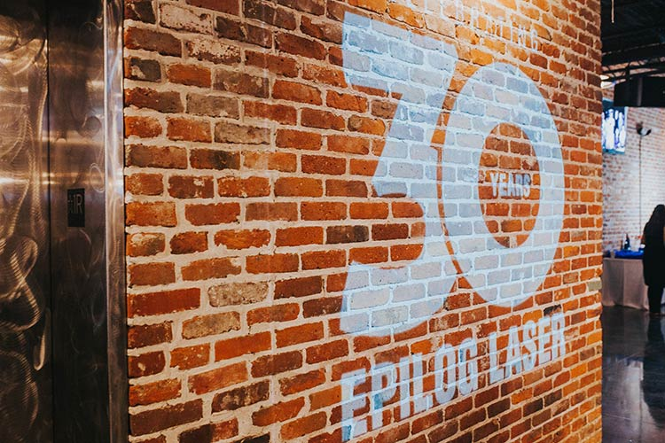 Epilog Laser 30th Anniversary logo projected onto a brick wall.