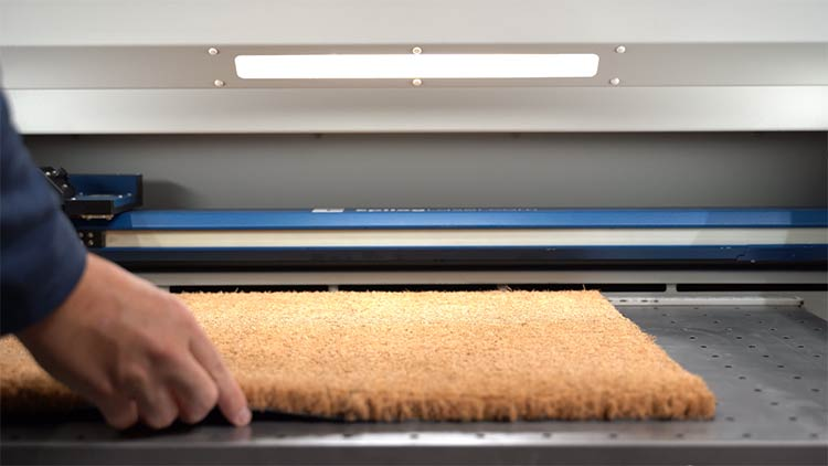 placing the coir doormat into the fusion pro laser