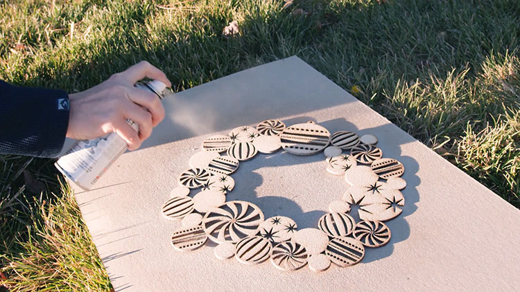 Spray painting a laser cut Christmas wreath.