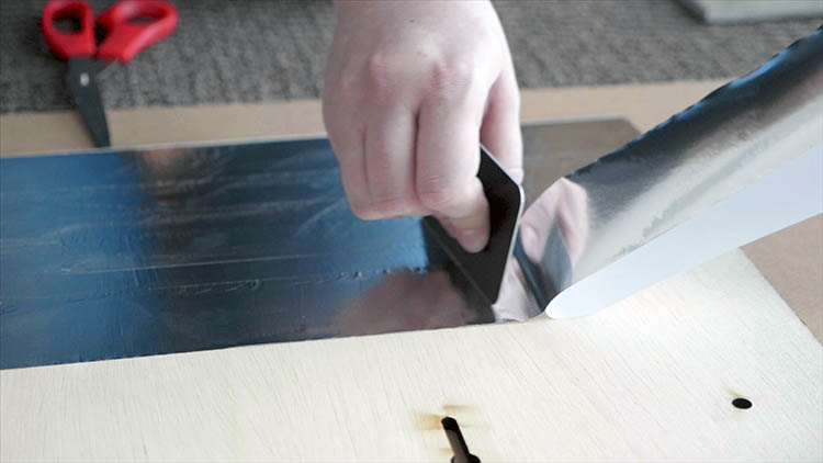 Applying foil tape to the back plywood panel.